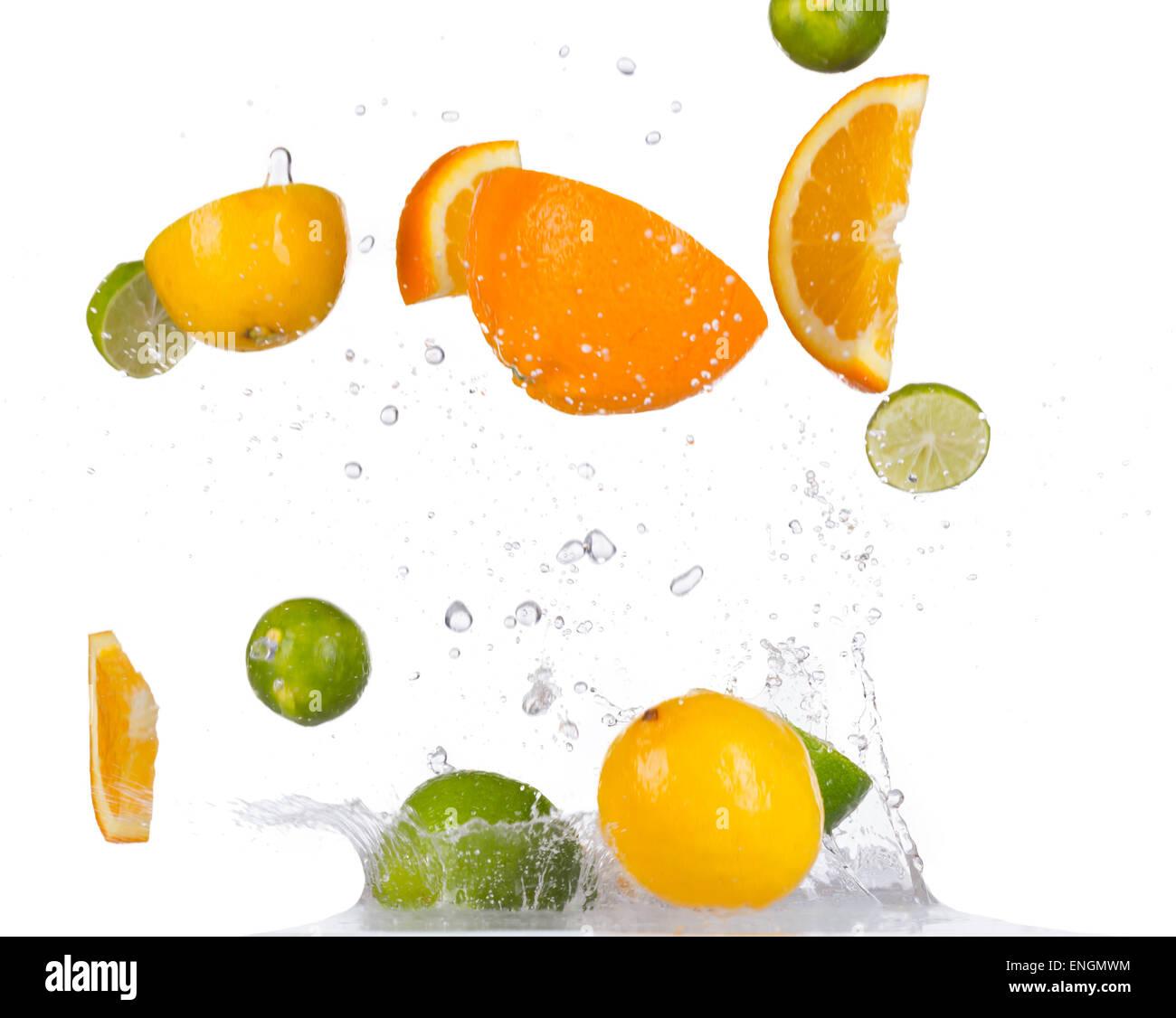 Fresh oranges, limes and lemons with water splashes isolated on black background - Stock Image
