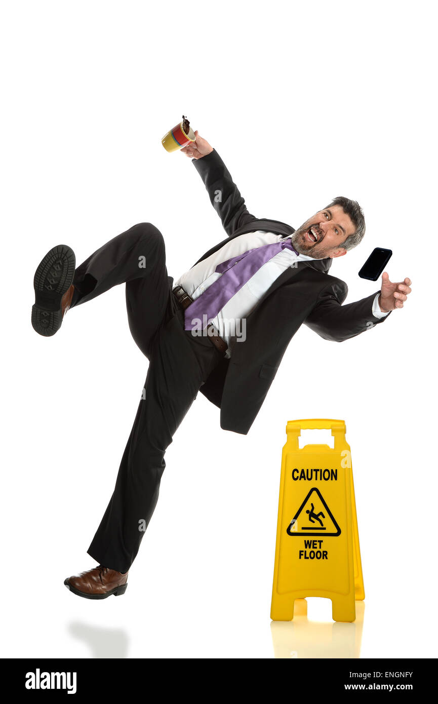 Hispanic businessman falling next to wet floor sign isolated over white background - Stock Image