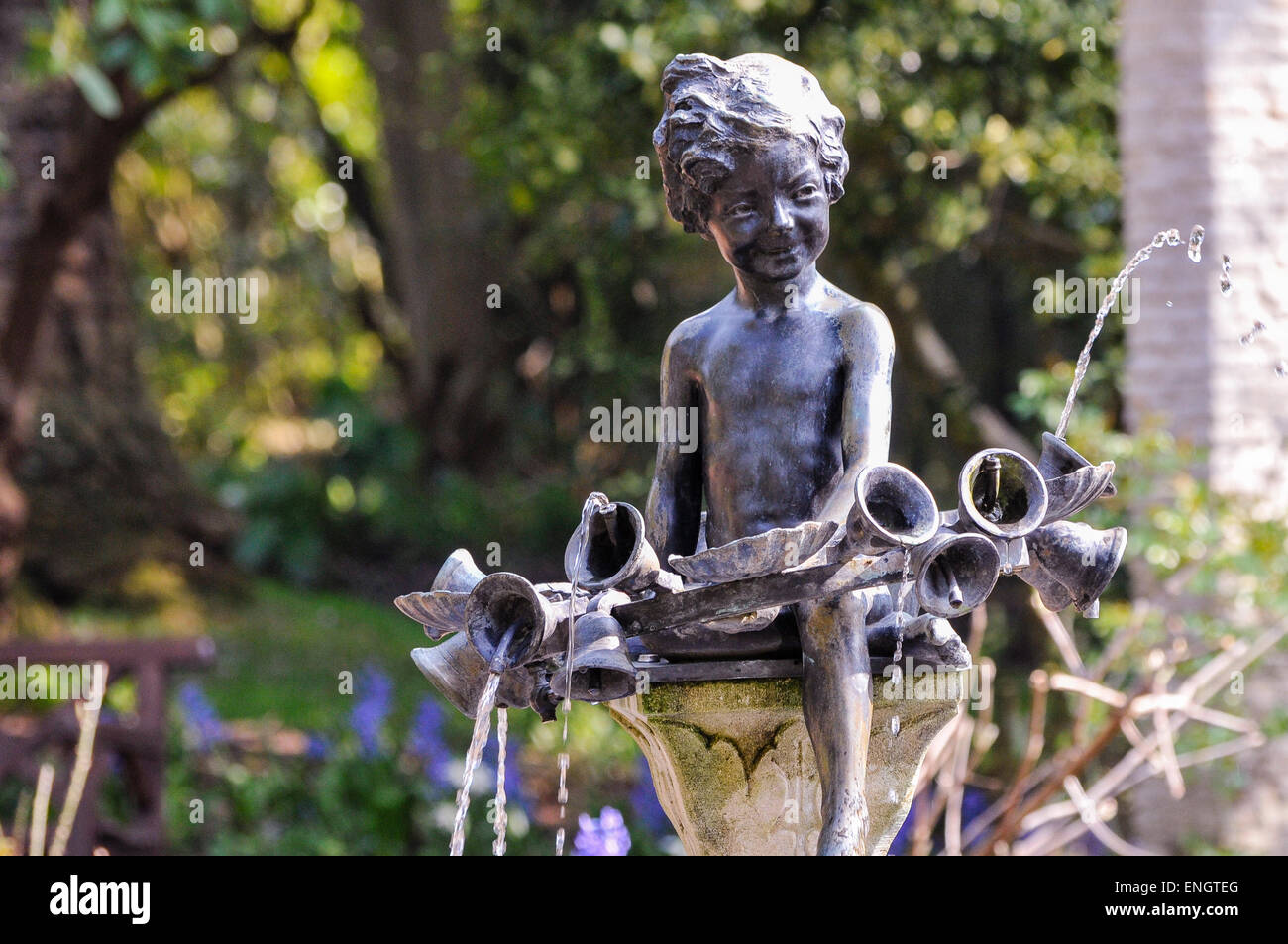 Bronze water fountain in the shape of a young boy with bells - Stock Image