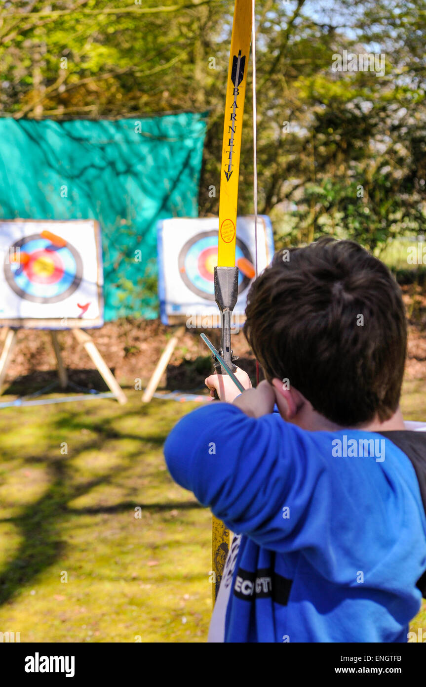 A young boy uses a bow and arrow during an archery session - Stock Image