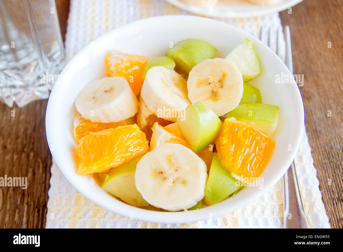 Fruit salad on wooden table, close up horizontal - Stock Image