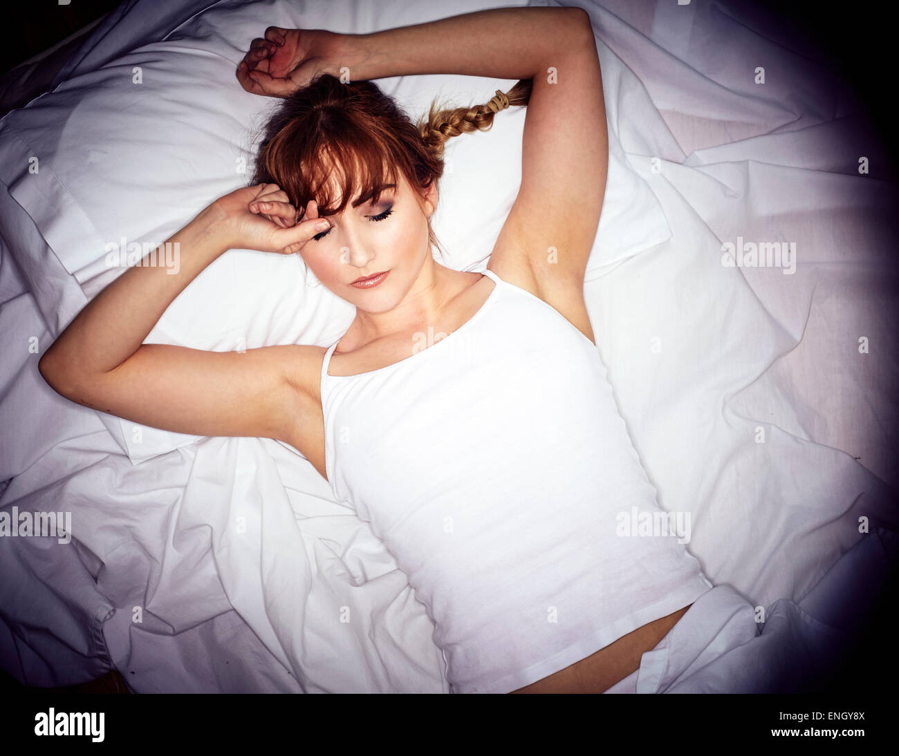 Girl laid in bed not able to sleep Stock Photo