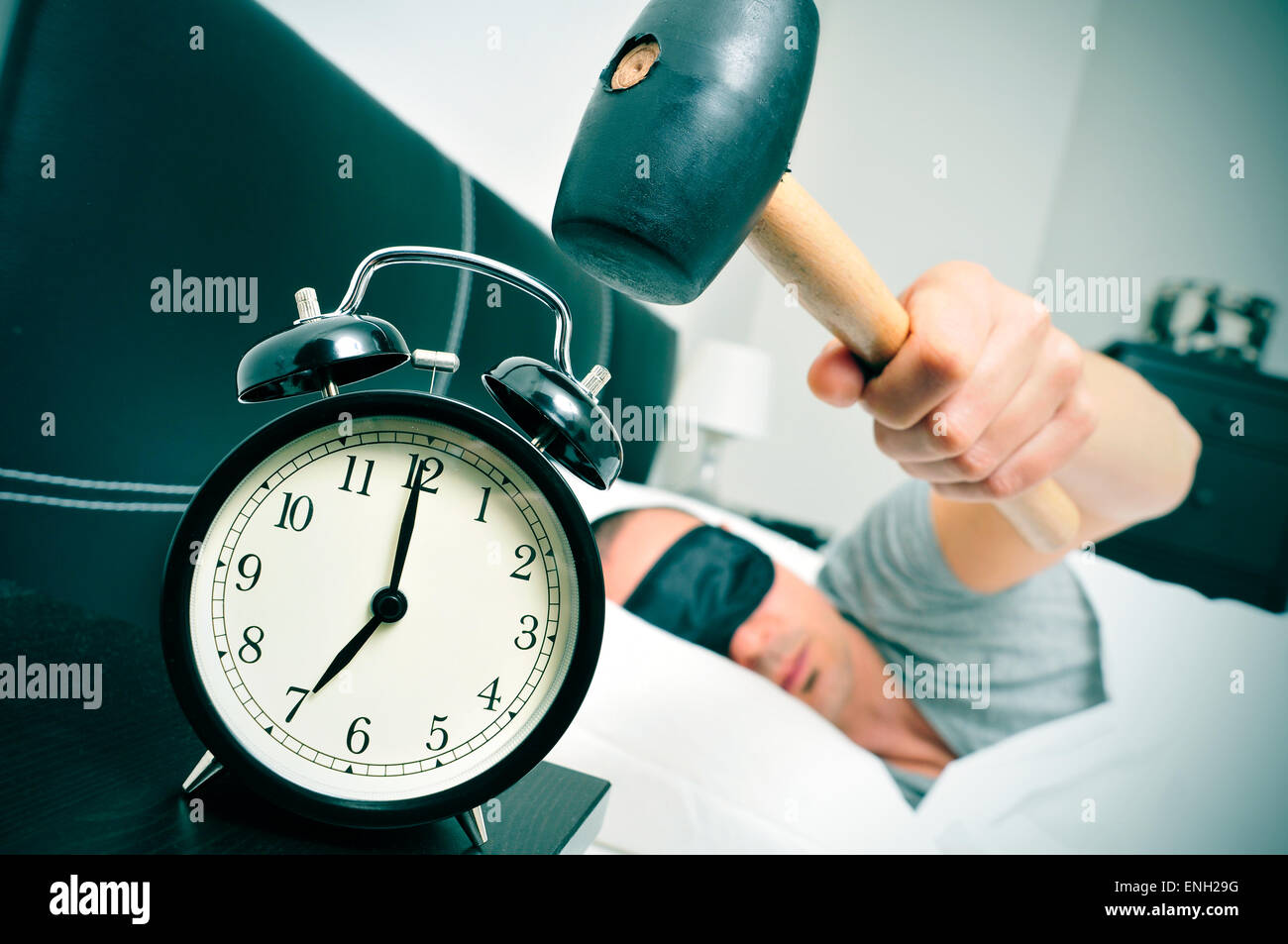 a young caucasian man in bed about to hammer his alarm clock at seven in the morning - Stock Image