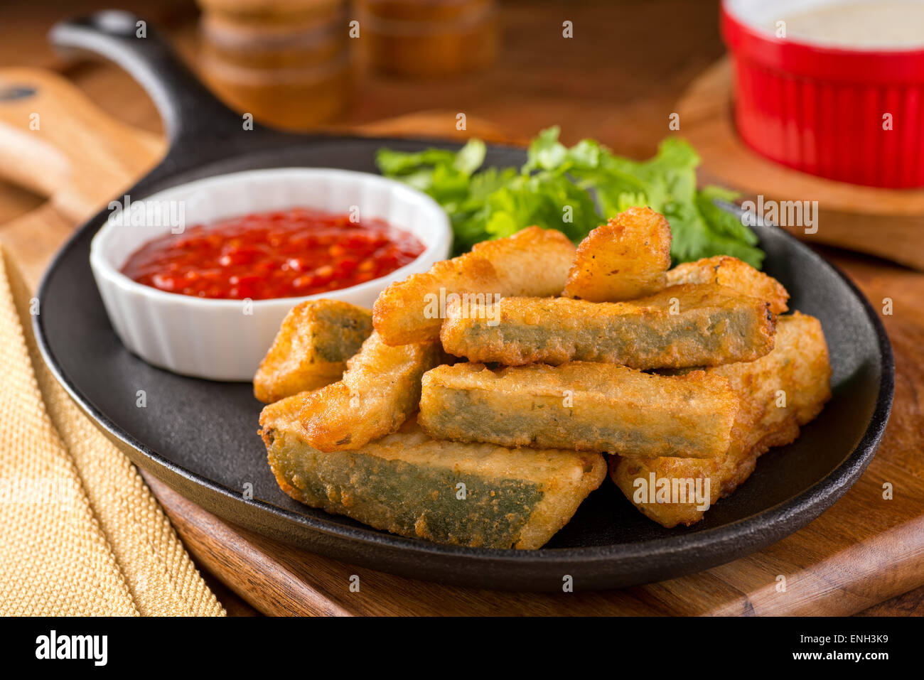 Delicious deep fried zucchini sticks with marinara dipping sauce. Stock Photo