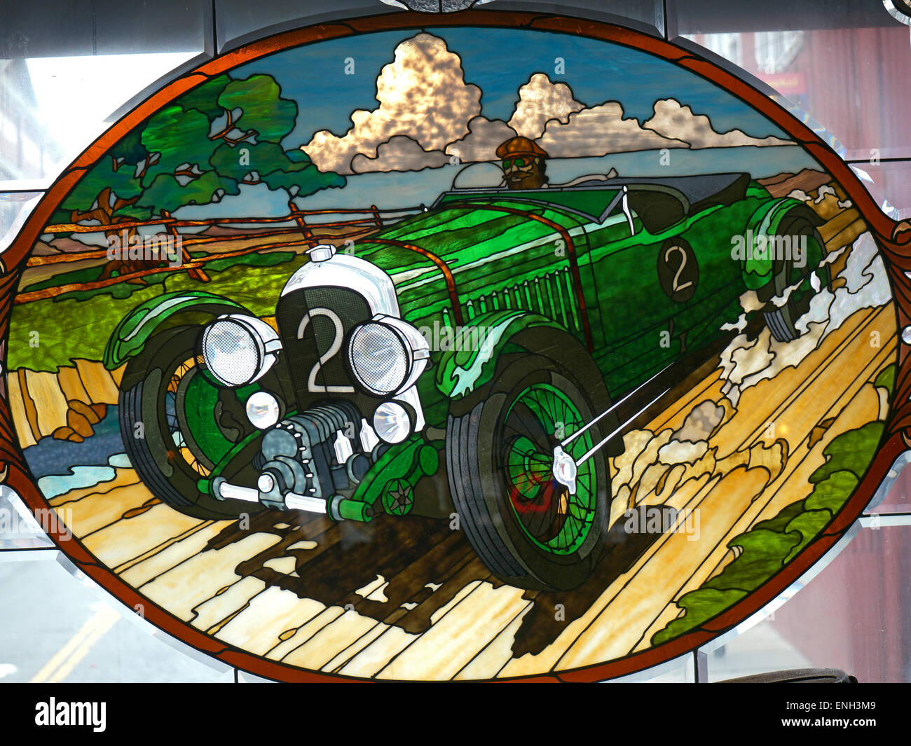 Stained glass window detail featuring Le Mans vintage 1920's 'Straight Eight' Bentley No 2  in auto themed bar in Stock Photo