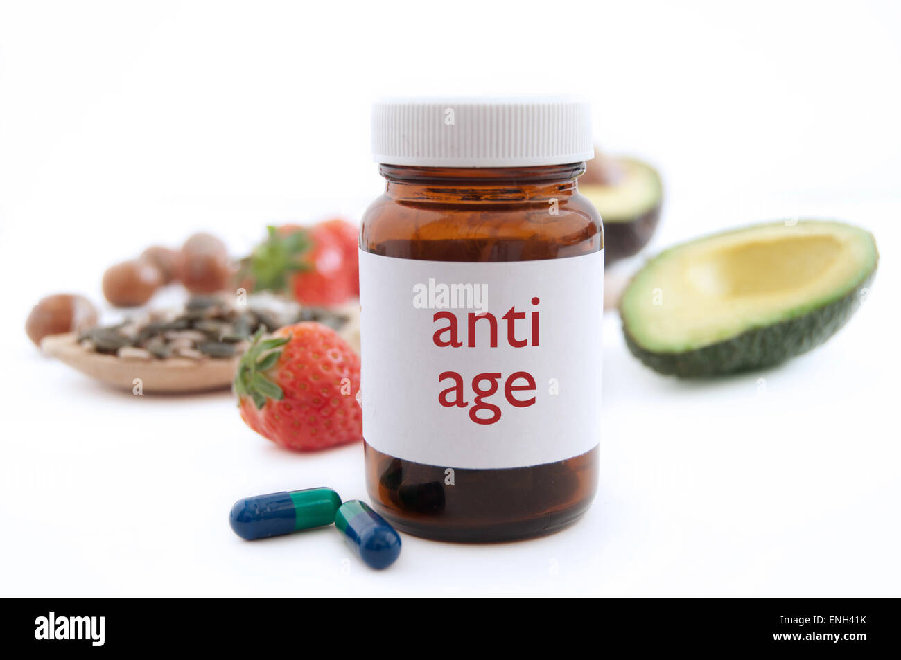 Medecine jar with anti aging pills surrounded by nutritious superfoods including avocado, pumpkin seeds and berries - Stock Image