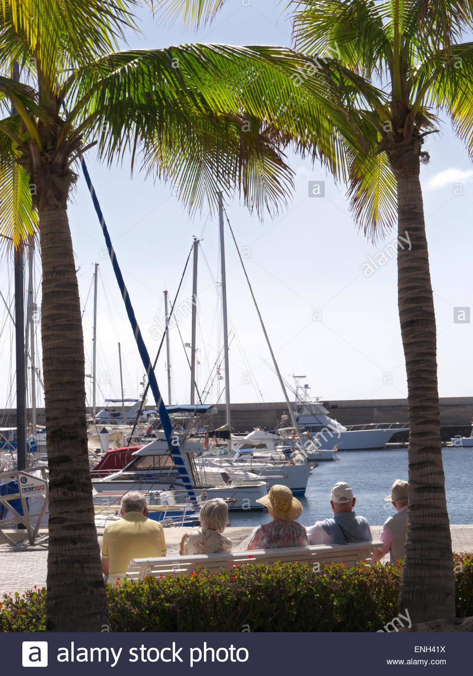Group of elderly pensioner holidaymakers sitting sunbathing on bench enjoying the marina view at Puerto Calero Lanzarote - Stock Image