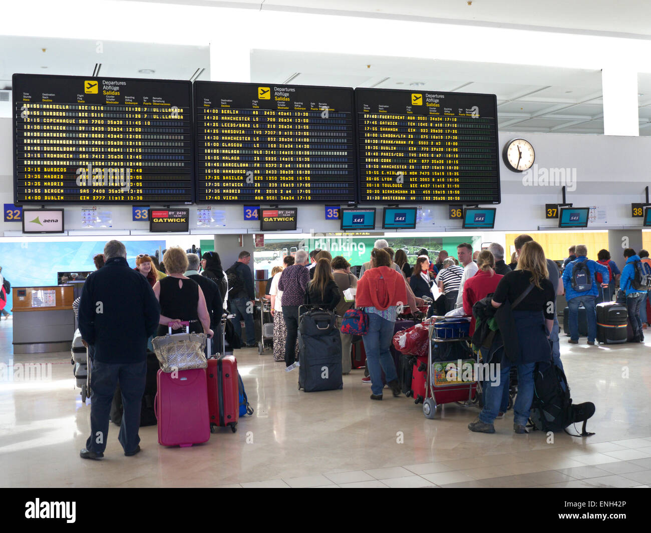 Information screens and queues of airline passengers and luggage wait on airport concourse to check in to their - Stock Image