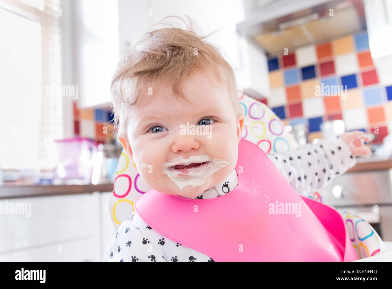 Six month old baby girl with messy face after feeding on porridge - Stock Image