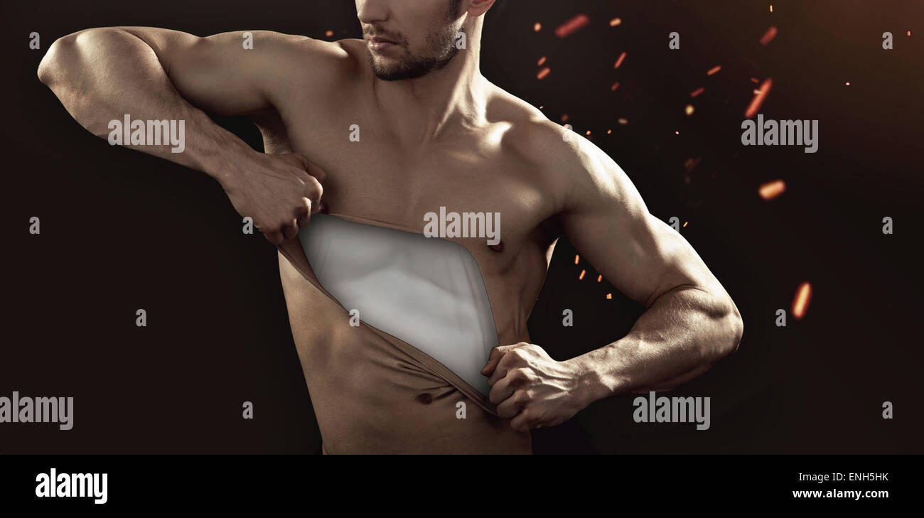 Muscular guy pulling his chest skin away - Stock Image