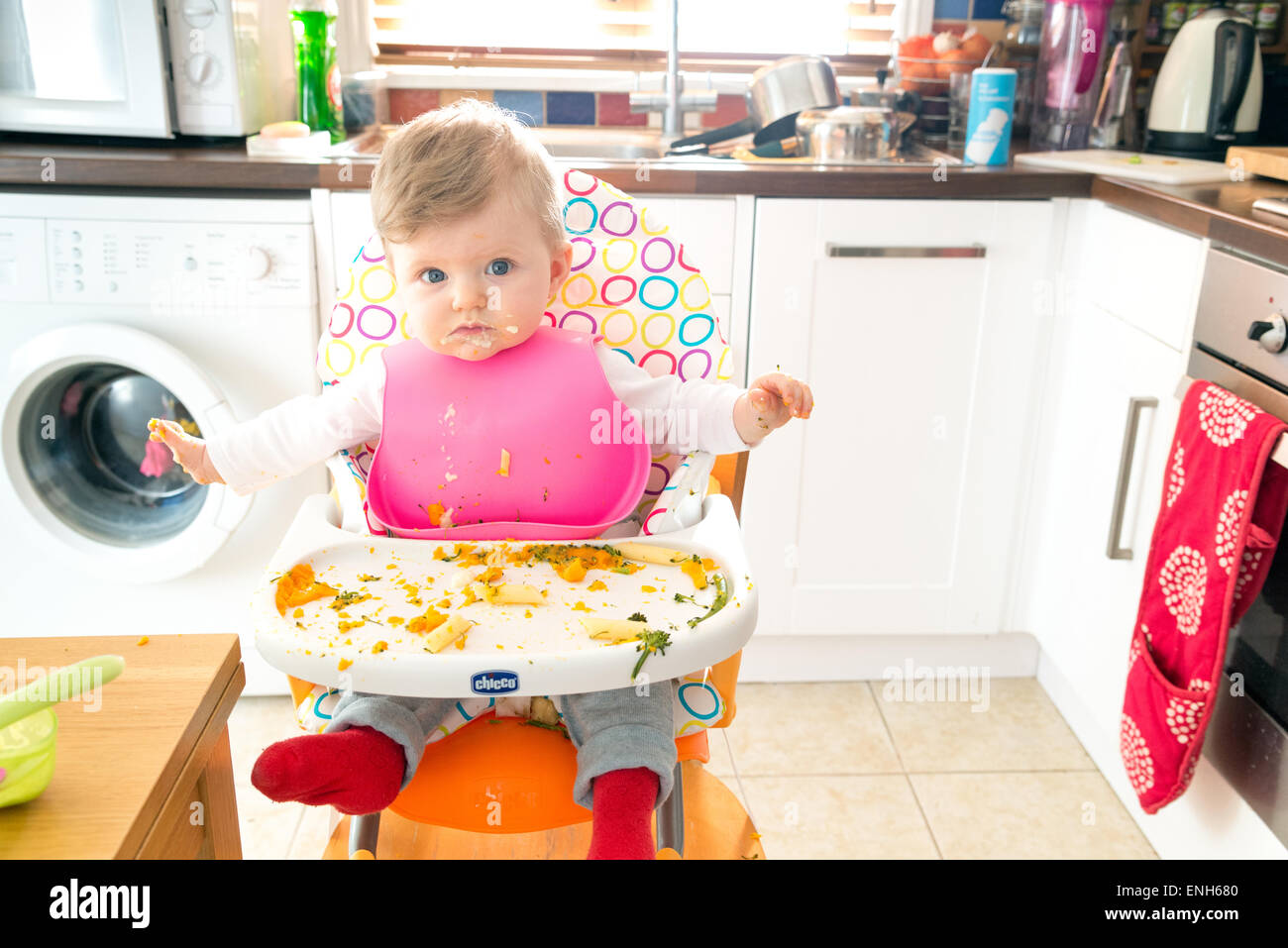 Baby led feeding a six month old baby eating messily - Stock Image