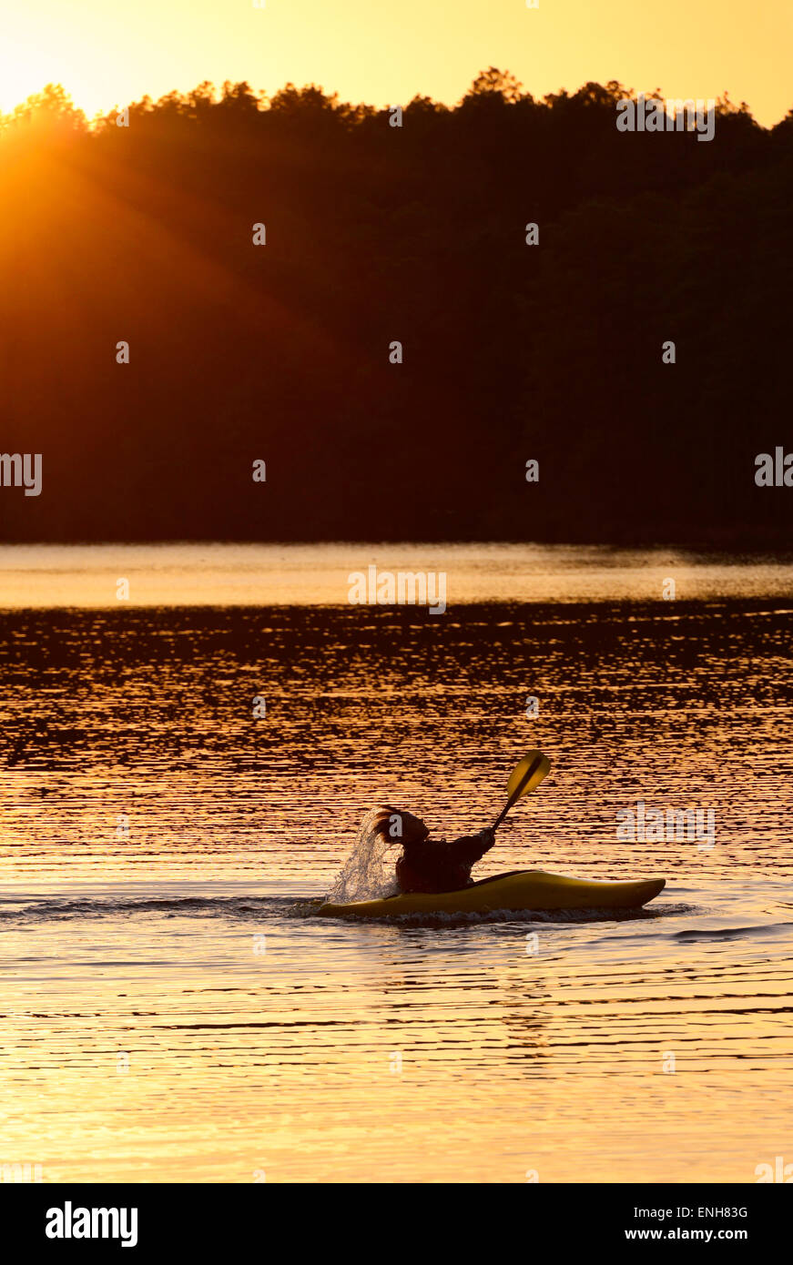 A kayaker silhouetted in the Sunset at 'Reservoir Park' Southern Pines, North Carolina, Moore County NC. - Stock Image