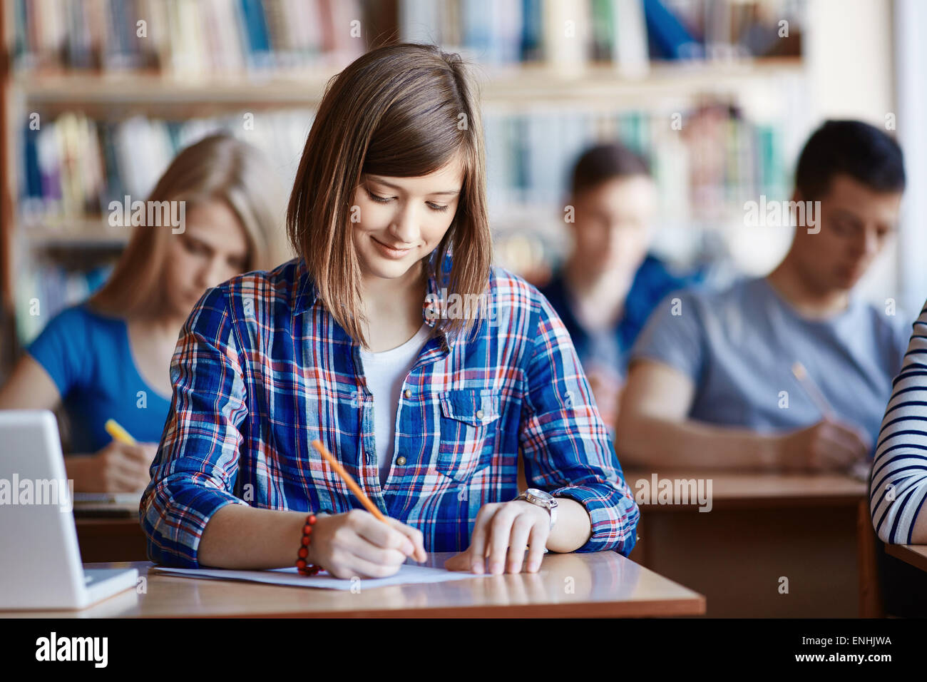 Highschool student carrying out task at workplace - Stock Image