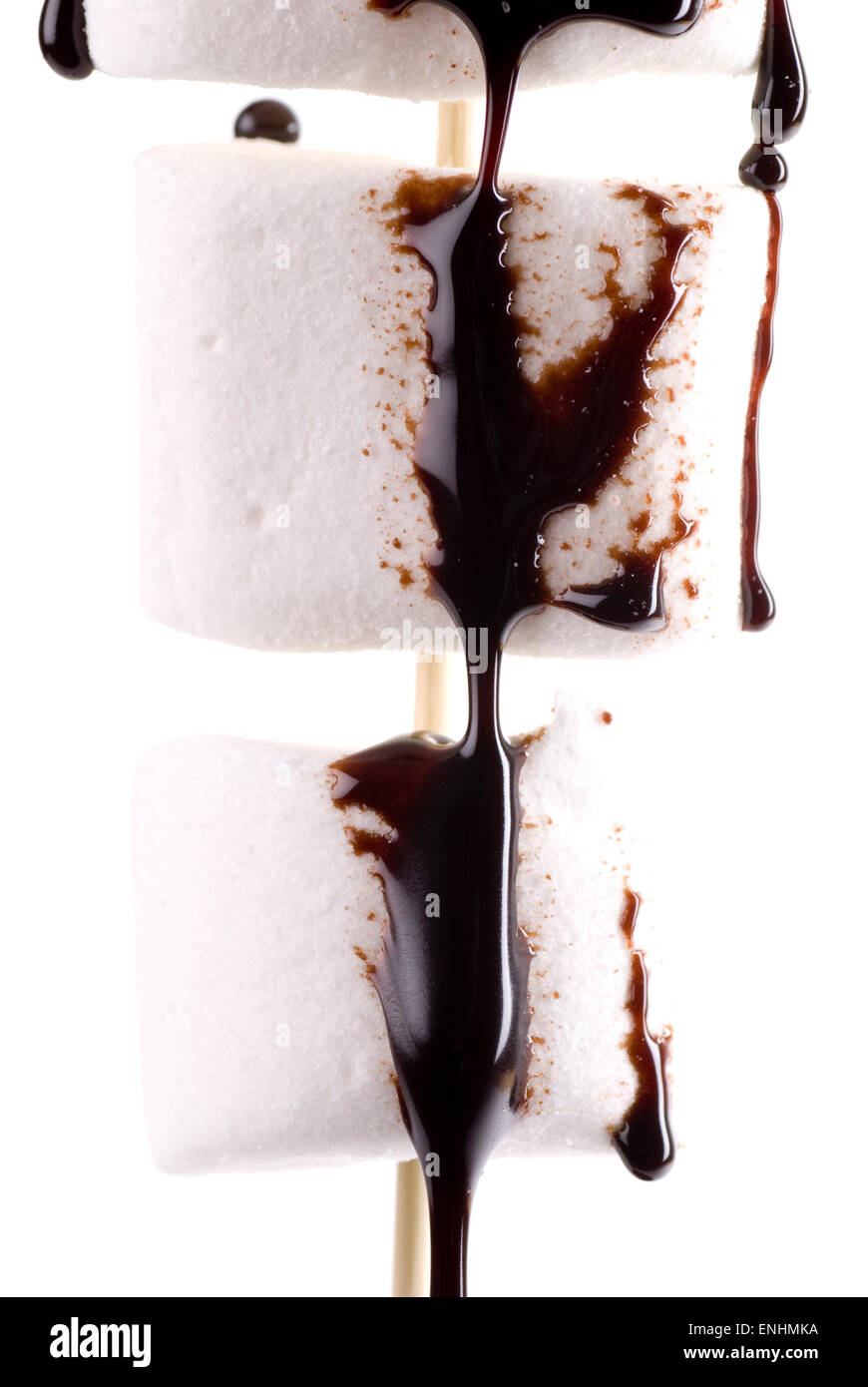 Marshmallows with chocolate sauce on a wooden stick. - Stock Image