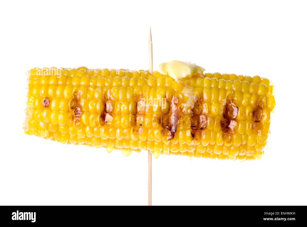 Grilled corn on the cob on a skewer with melted butter and salt. - Stock Image