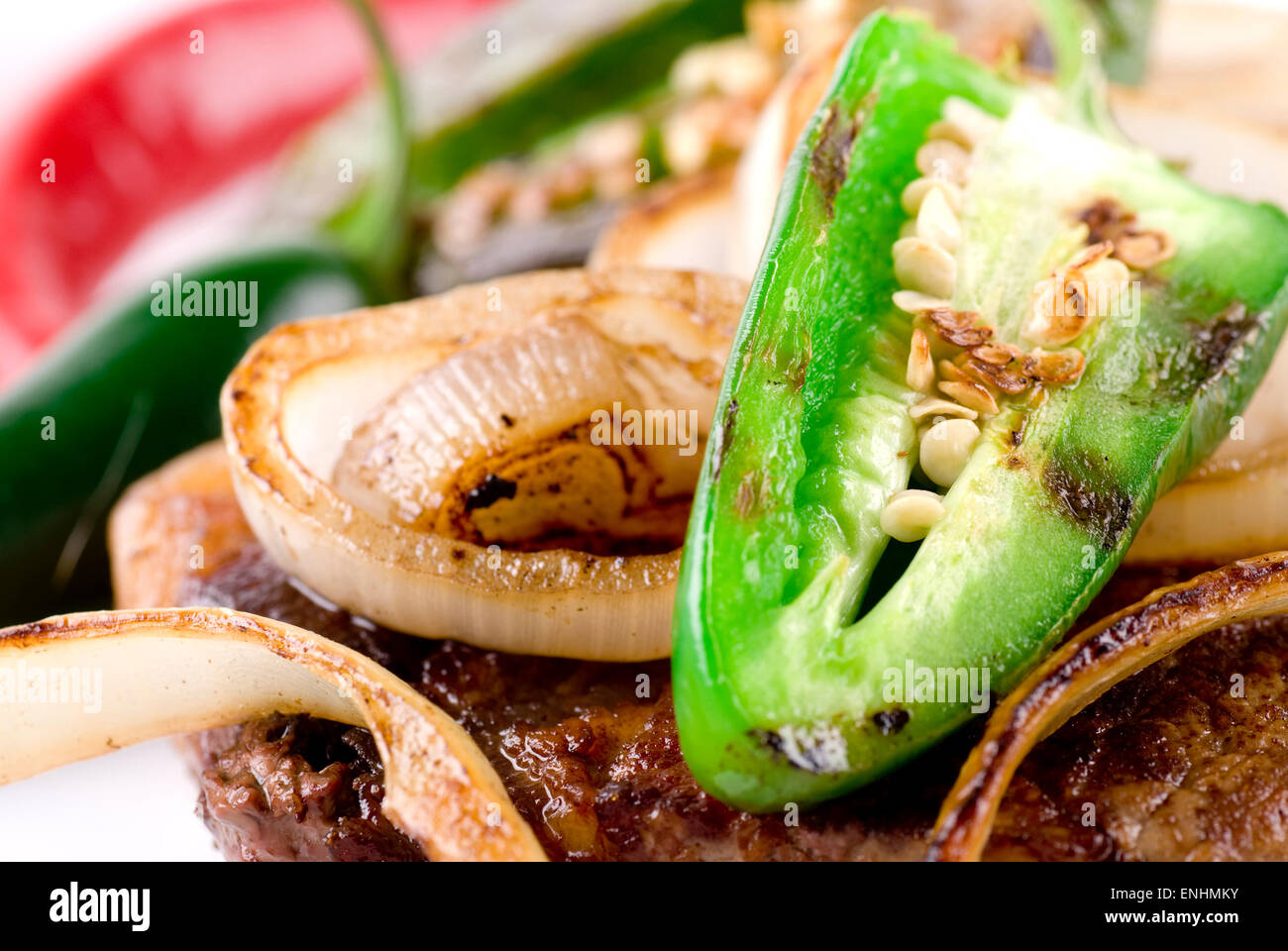 Beef steak with jalapeno and sliced onion close up. - Stock Image