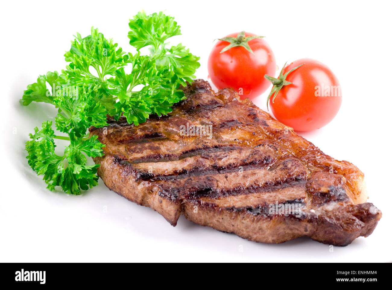 Grilled steak with fresh parsley on white plate. - Stock Image