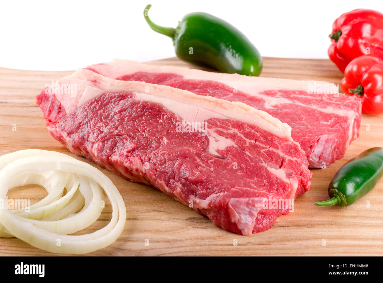 Two steaks with habanero, sliced onion and jalapeno. - Stock Image