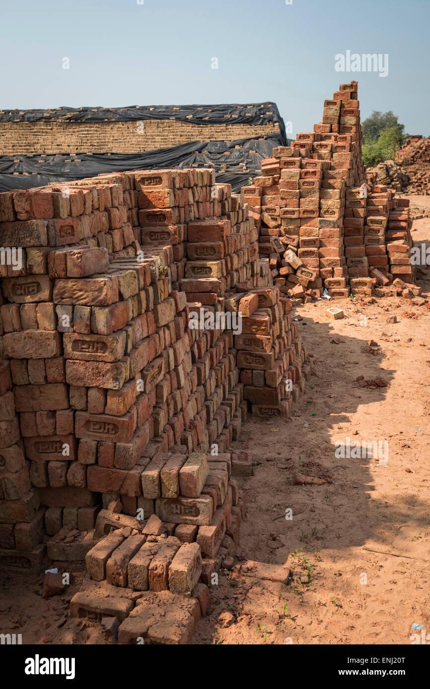 Stacks of newly fired bricks at a brick works in Uttar Pradesh, India - Stock Image