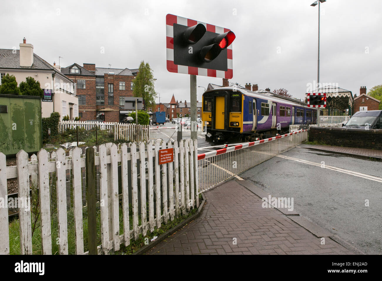 a Northern Rail train passes through a level crossing in Hale , Greater Manchester - Stock Image