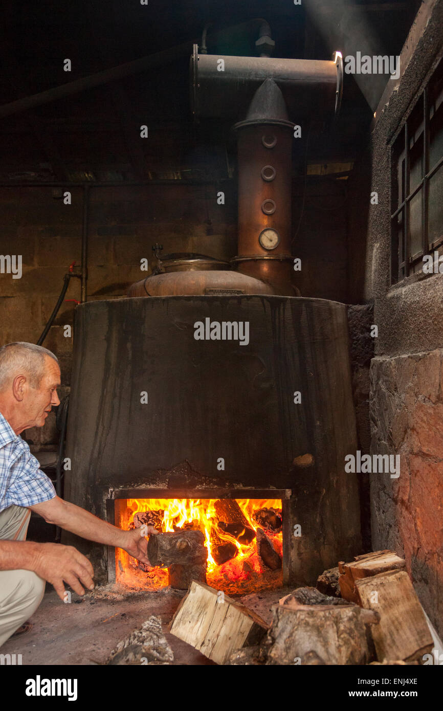 Man adding logs to the fire of a Pot Still.Heat is applied directly to the wine to produce homemade grape brandy,Melnik,South - Stock Image