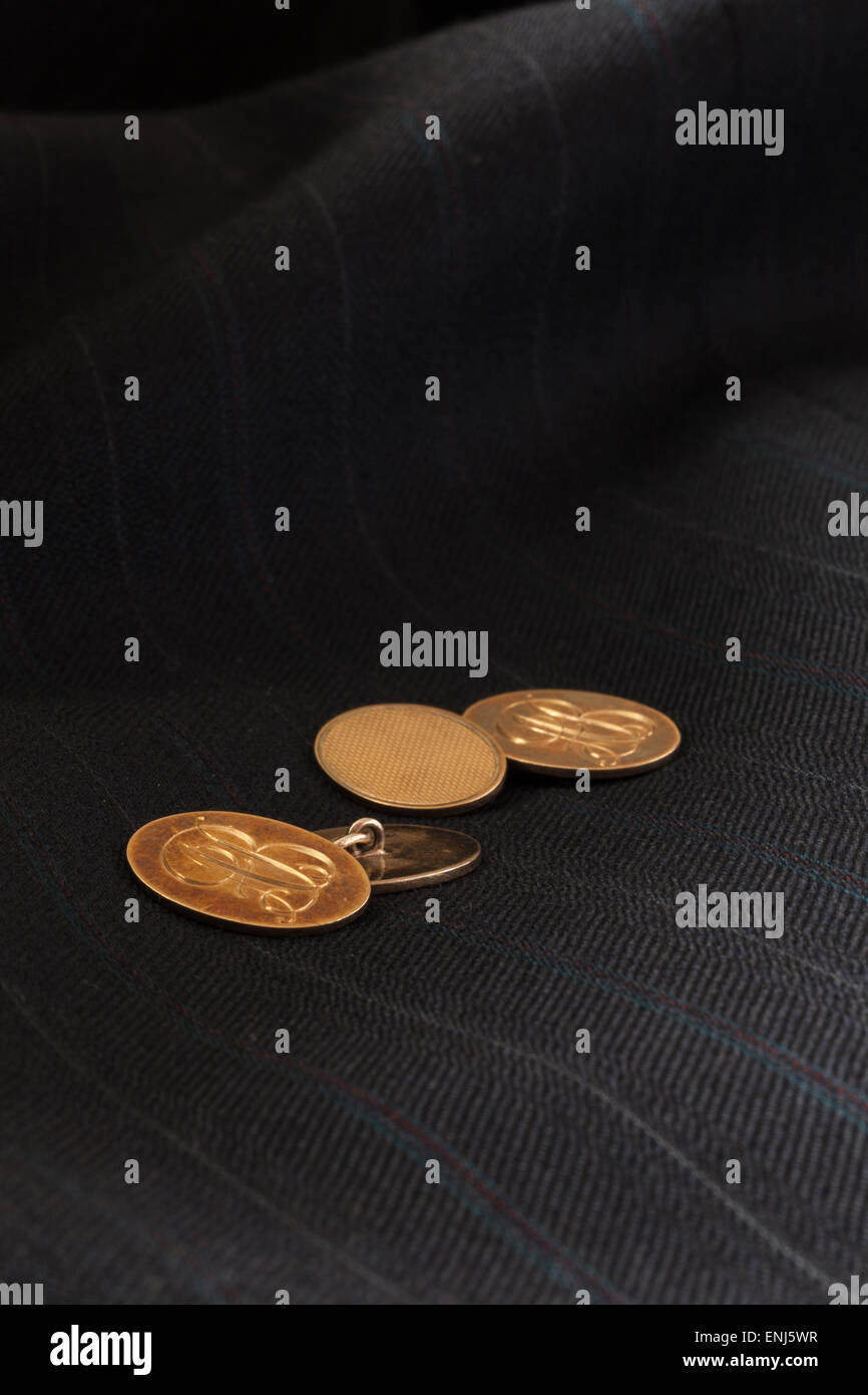 9ct Gold on silver Cuff Links, engraved with initials 'A B', with a dark suit jacket as the background, - Stock Image