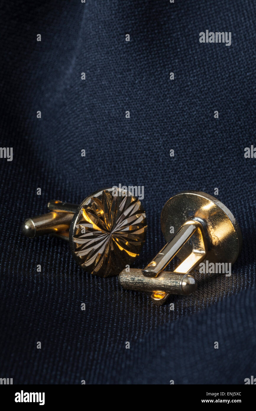 22ct Gold plated Cuff Links with a decorative diamond cut pattern on a dark suit jacket background, shot in natural - Stock Image