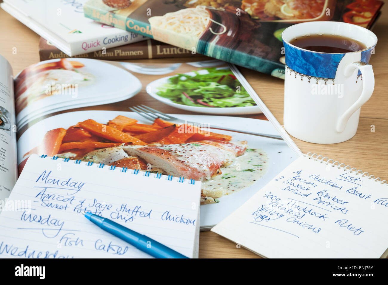 A notepad with weekly meal plan and shopping list on a table top beside an open cookery book and a mug of coffee. - Stock Image