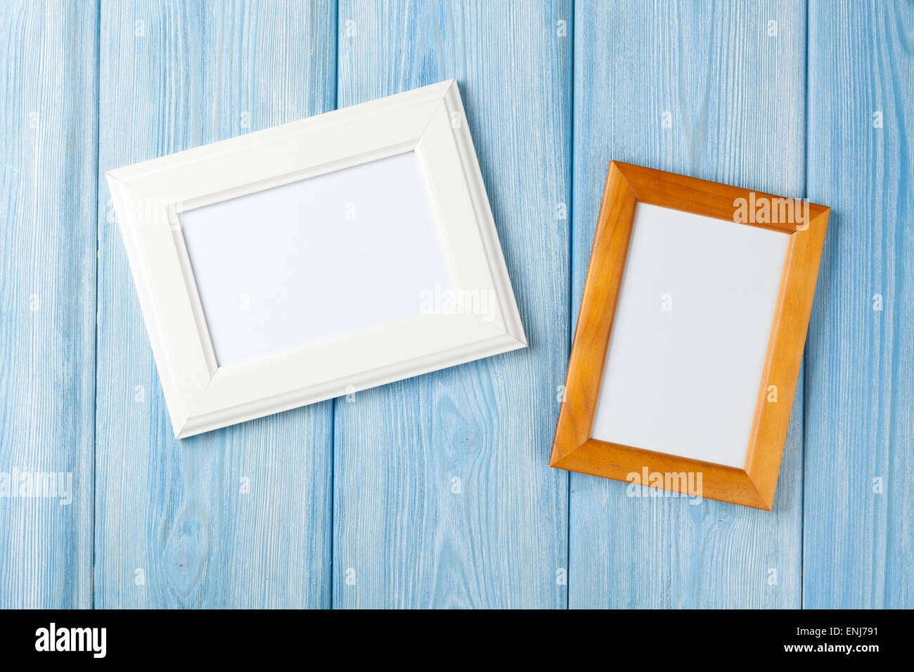 Photo frames on blue wooden wall with copy space - Stock Image