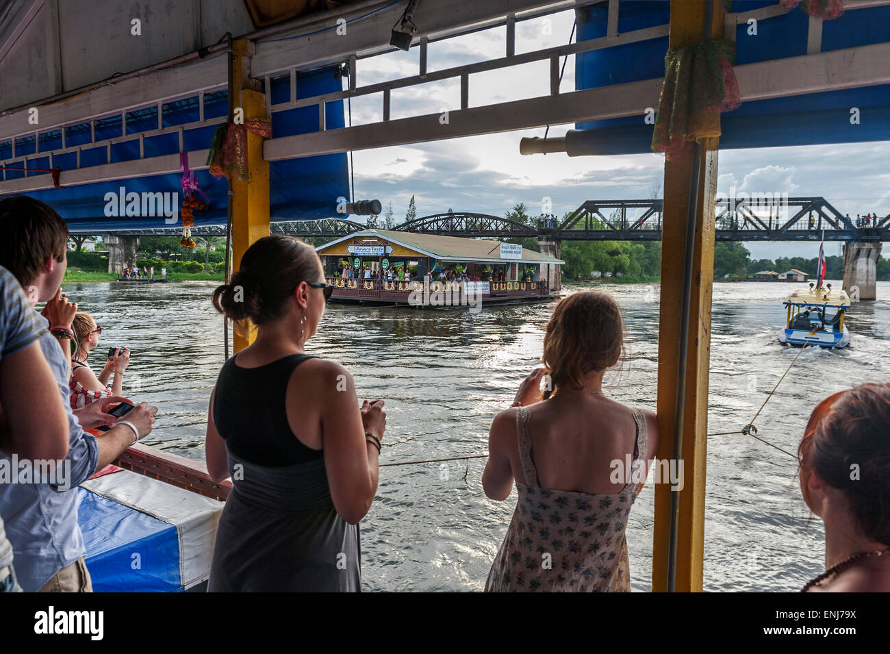 Tourists on a boat floating towards the bridge over the river Kwai. Kanchanaburi. Thailand - Stock Image