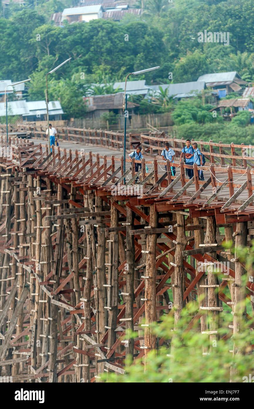 Local schoolchildren crossing the rickety wooden bridge (Saphan Mon) Sangkhlaburi. Kanchanaburi Province. Thailand. - Stock Image