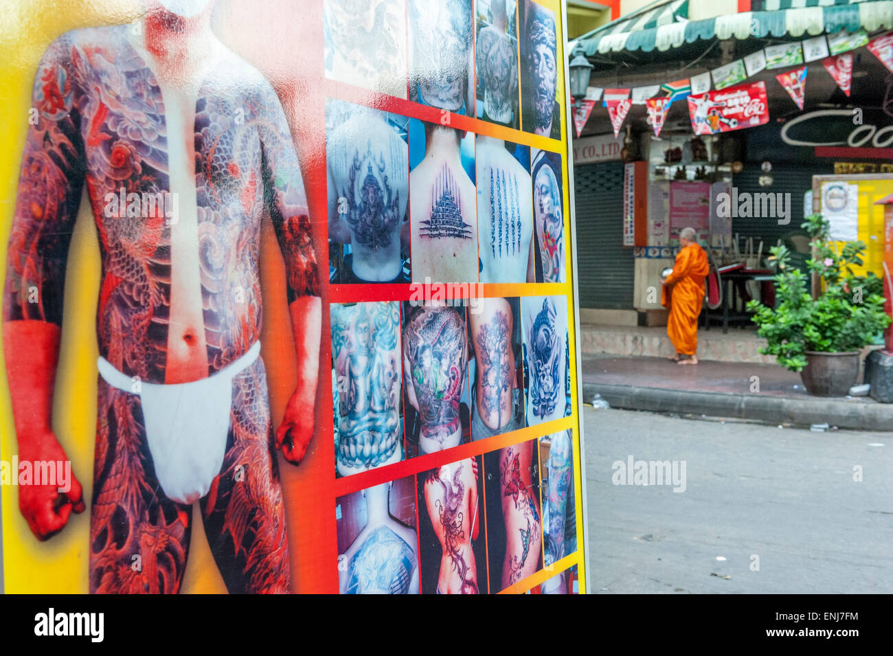 Buddhist monk on his morning alms round passing a large display for a tattoo studio. Bangkok. Thailand - Stock Image