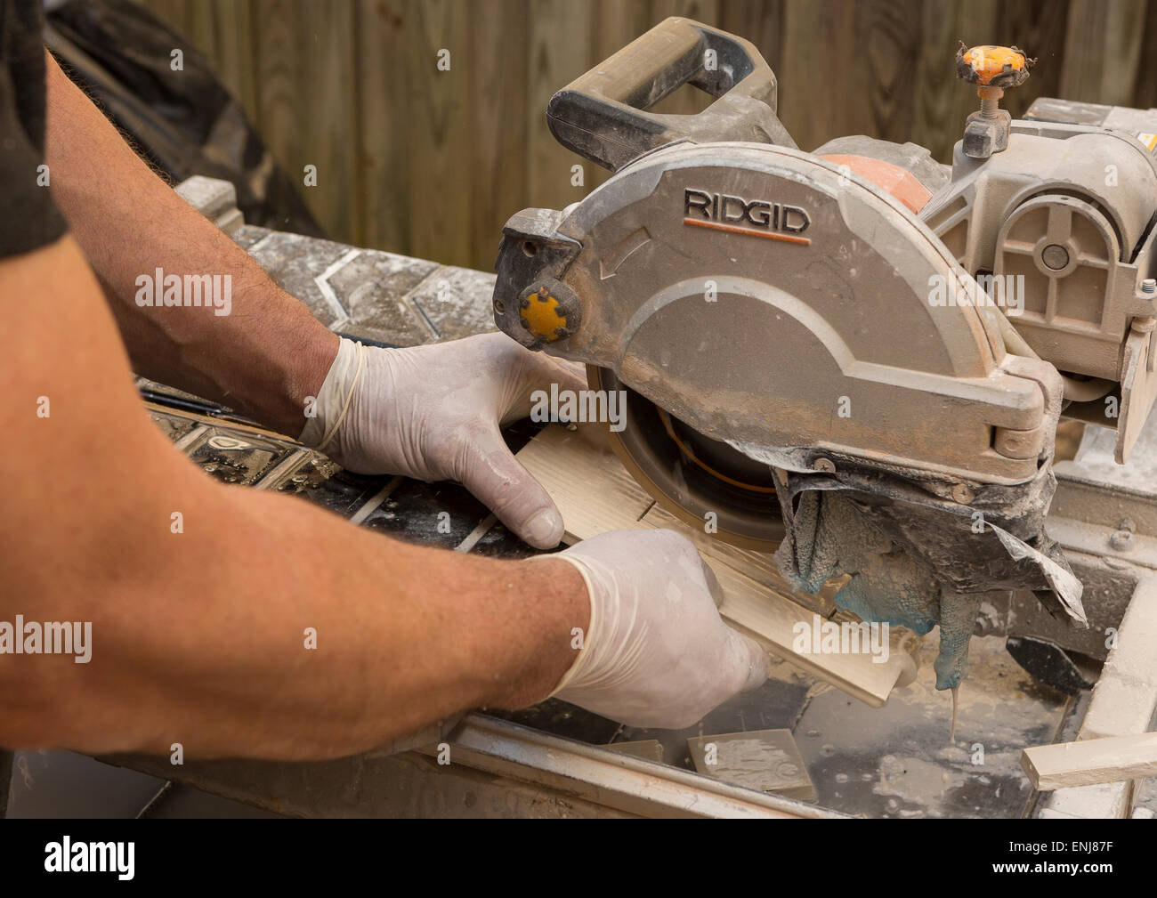 ARLINGTON, VIRGINIA, USA - Worker wearing latex gloves cuts ceramic tiles with a wet tile saw. - Stock Image