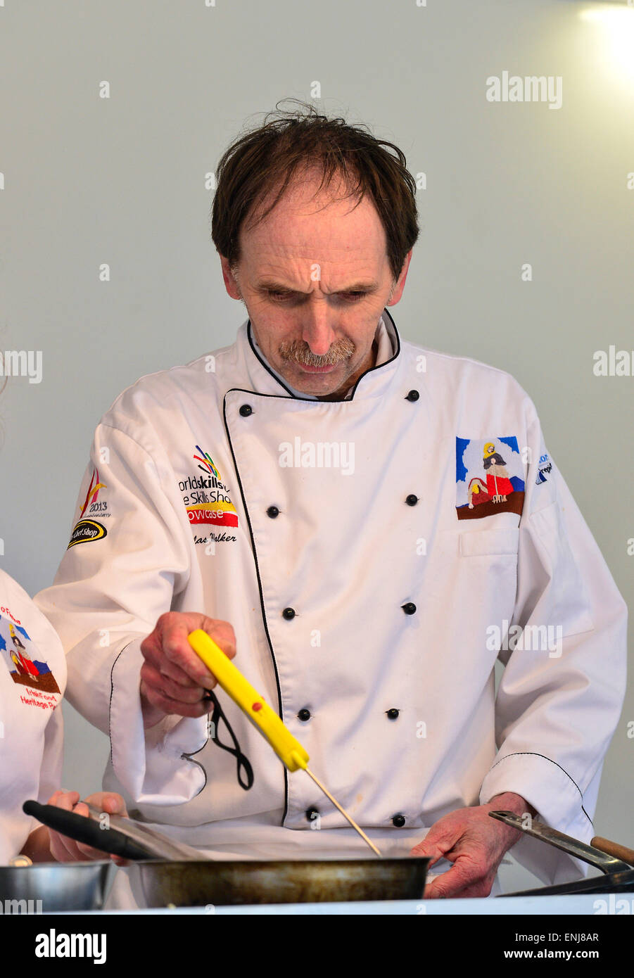 Chef using digital Folding Probe Thermometer to check temperature of hot food at cookery demonstration in Londonderry - Stock Image