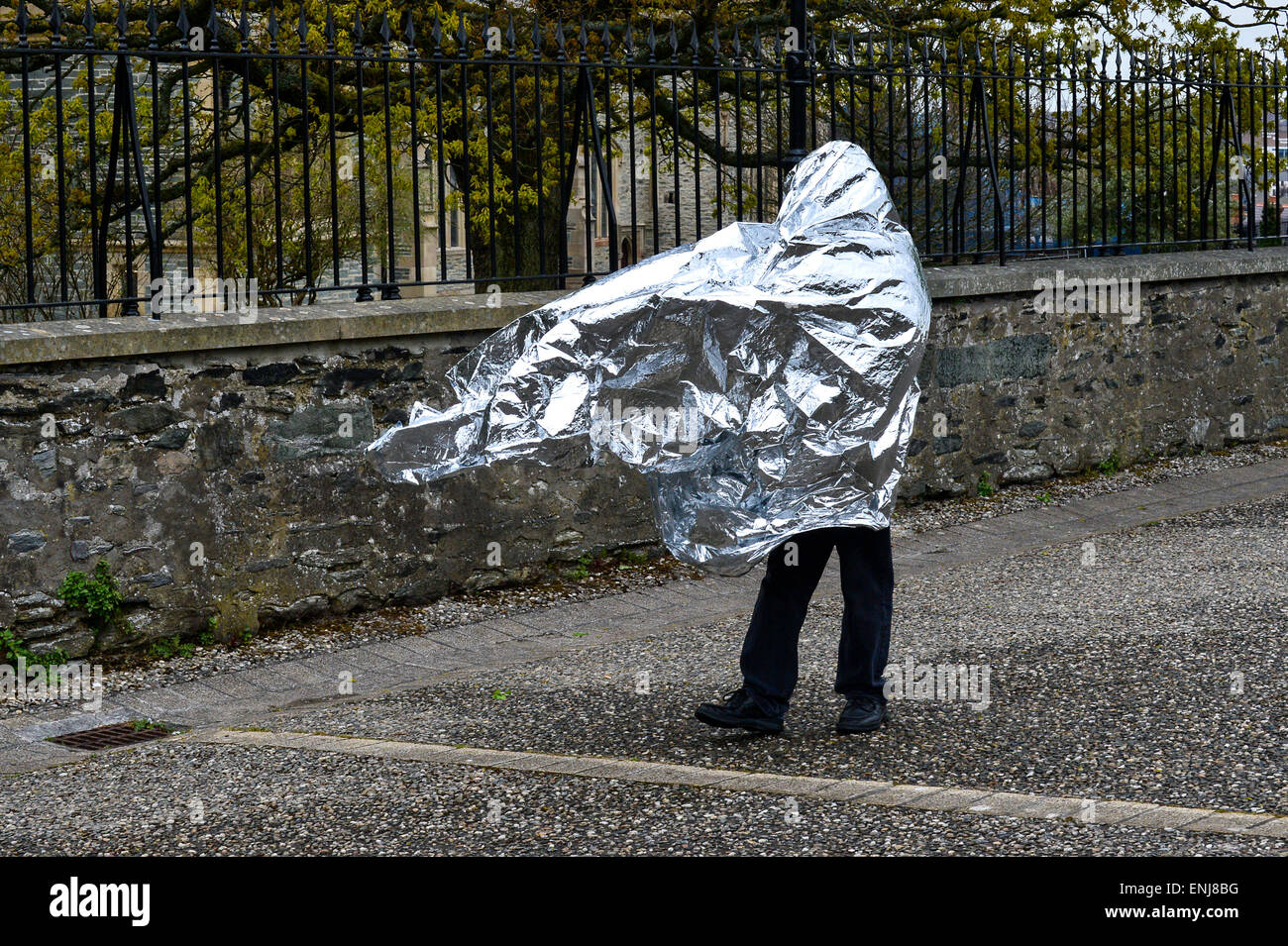 A man covered in a silver foil sheet walking along Derry Walls in Londonderry - Stock Image