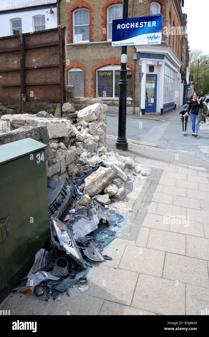 Rochester, Kent, England, UK. Wall damaged by a car crash, with pieces of the car, next to a 'Please Drive Carefully' - Stock Image