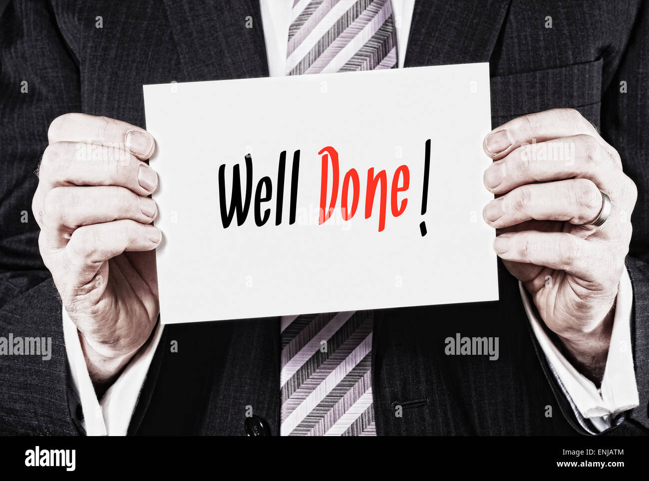 A businessman holding a card with the words, Well Done! written on it. - Stock Image