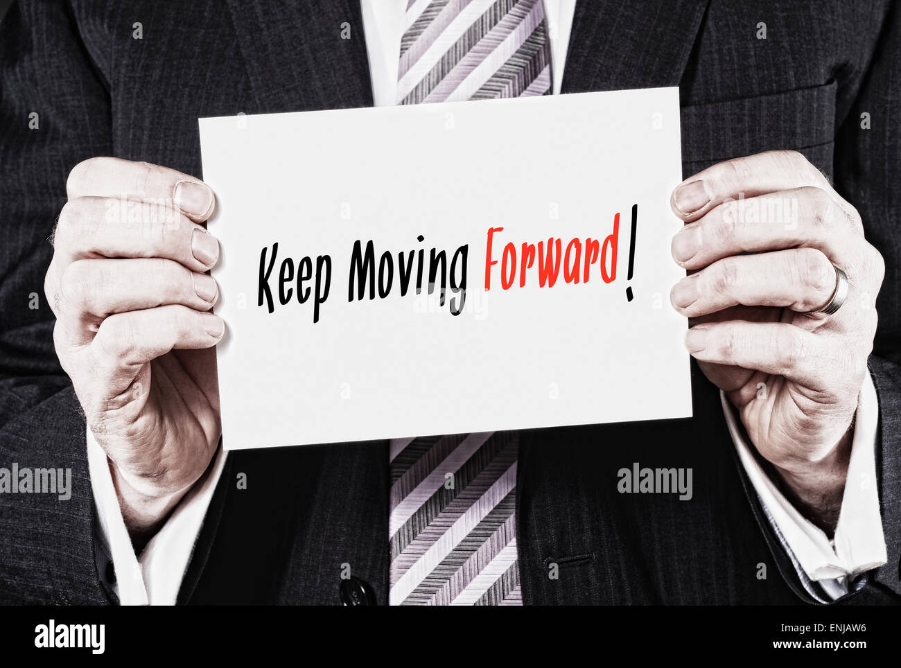 A businessman holding a card with the words, Keep Moving Forward. - Stock Image