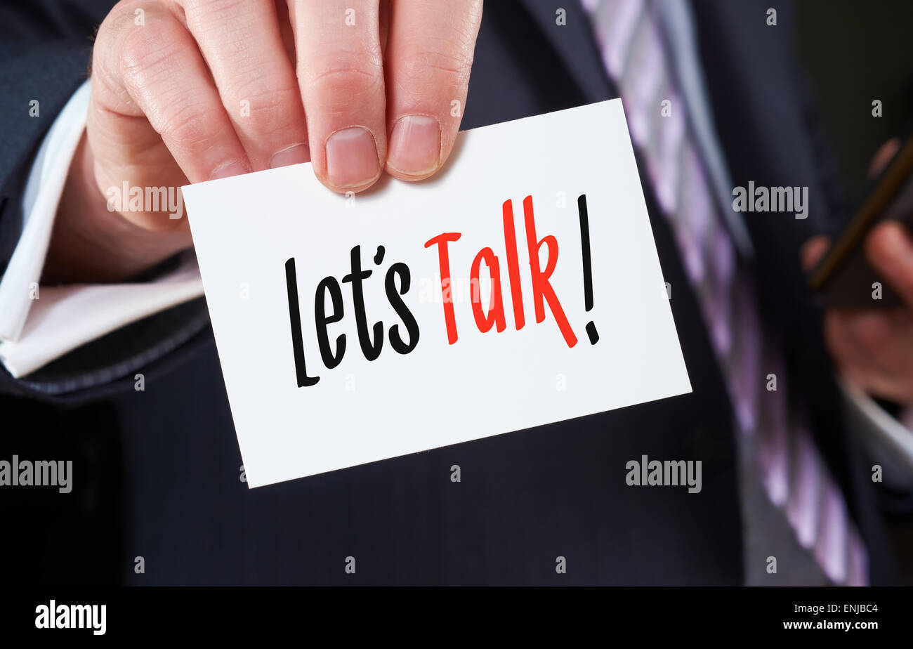A businessman holding a business card with the words, Let's Talk, written on it. - Stock Image