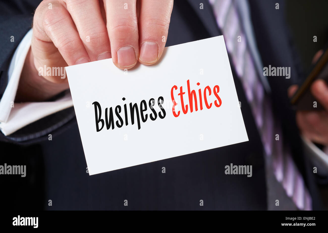 A businessman holding a business card with the words, Business Ethics, written on it. - Stock Image