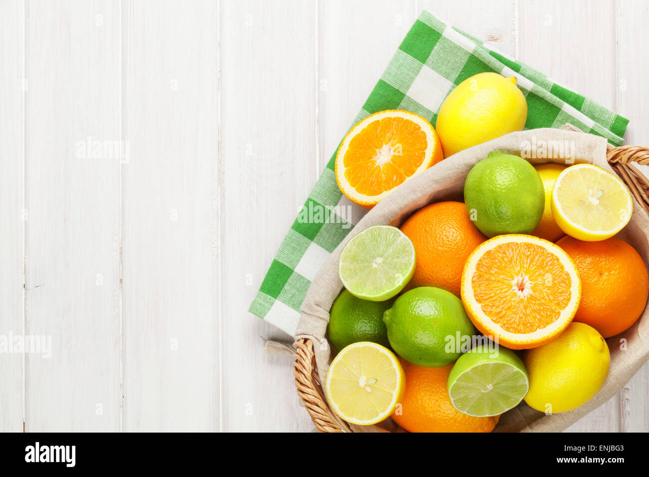 Citrus fruits in basket. Oranges, limes and lemons. Over white wood table background with copy space - Stock Image
