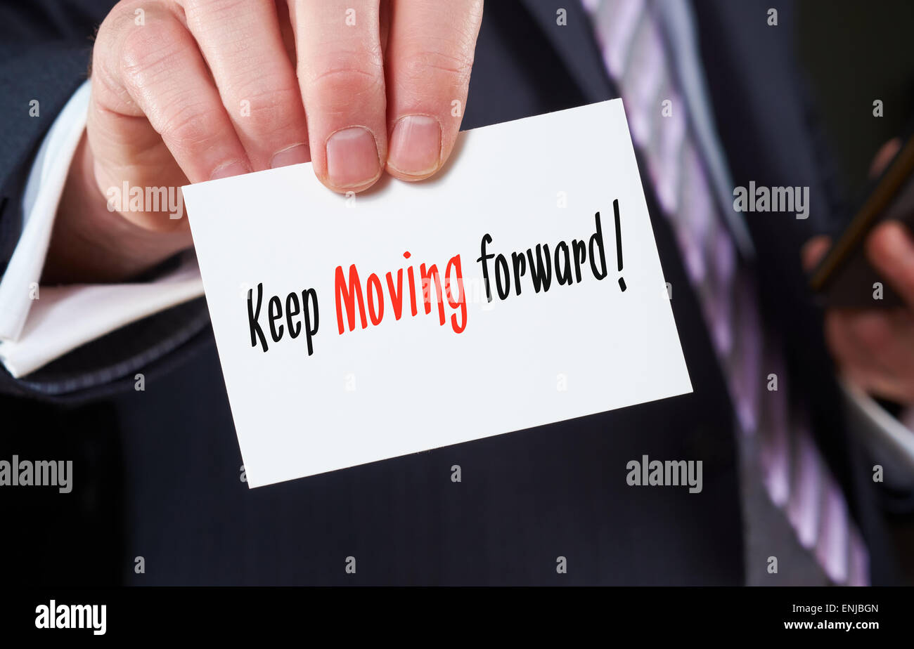 A businessman holding a business card with the words, Keep Moving Forward. - Stock Image