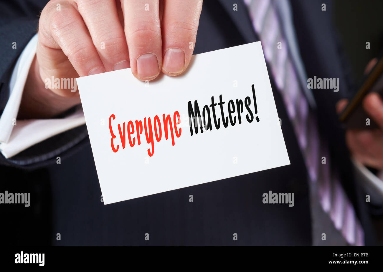 A businessman holding a business card with the words,  Everyone Matters. - Stock Image