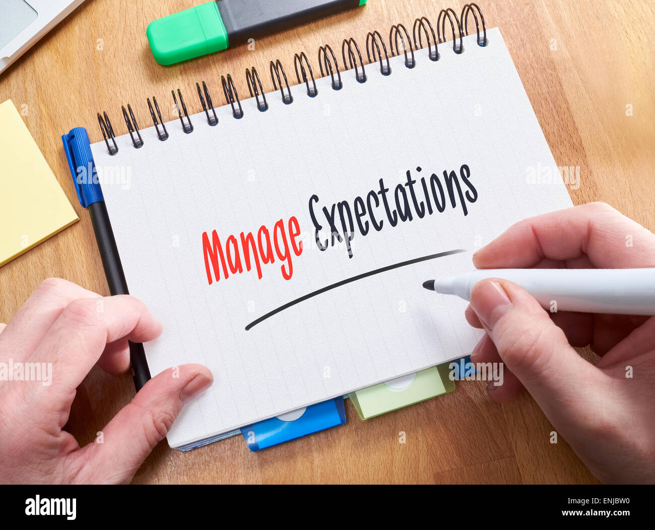 A businessman writing the words, Manage Expectations, on a note pad. - Stock Image