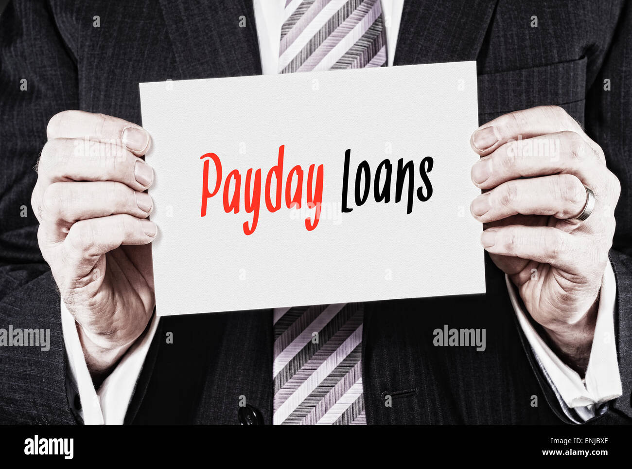 A businessman holding a business card with the words, Payday Loans, written on it. - Stock Image