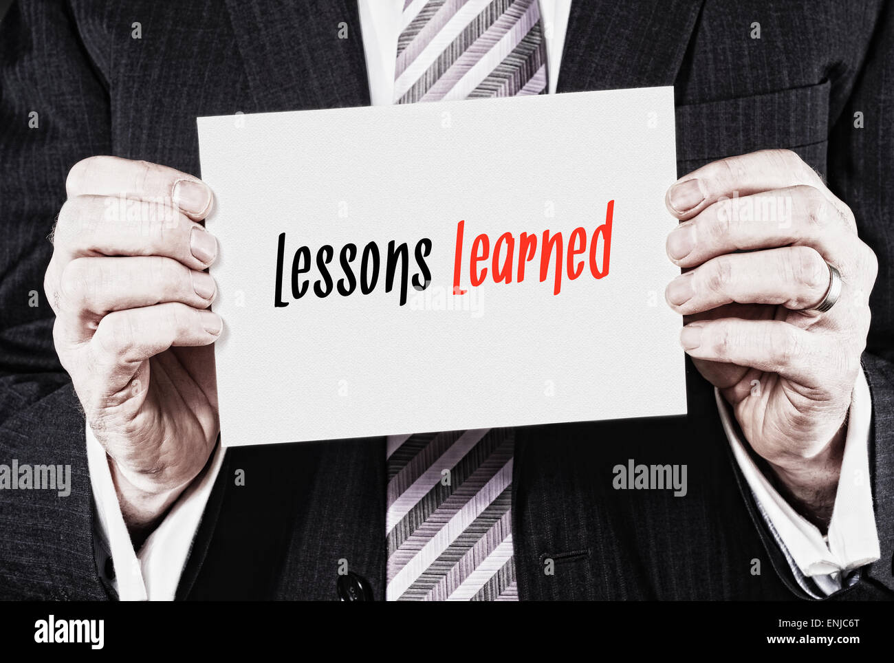 A businessman holding a business card with the words,  Lessons Learned, written on it. - Stock Image