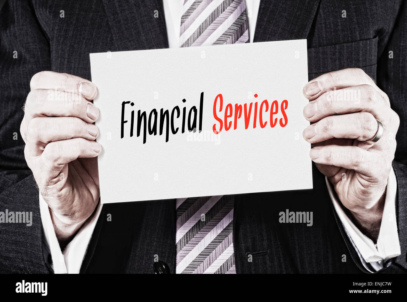 A businessman holding a business card with the words, Financial Services, written on it. - Stock Image