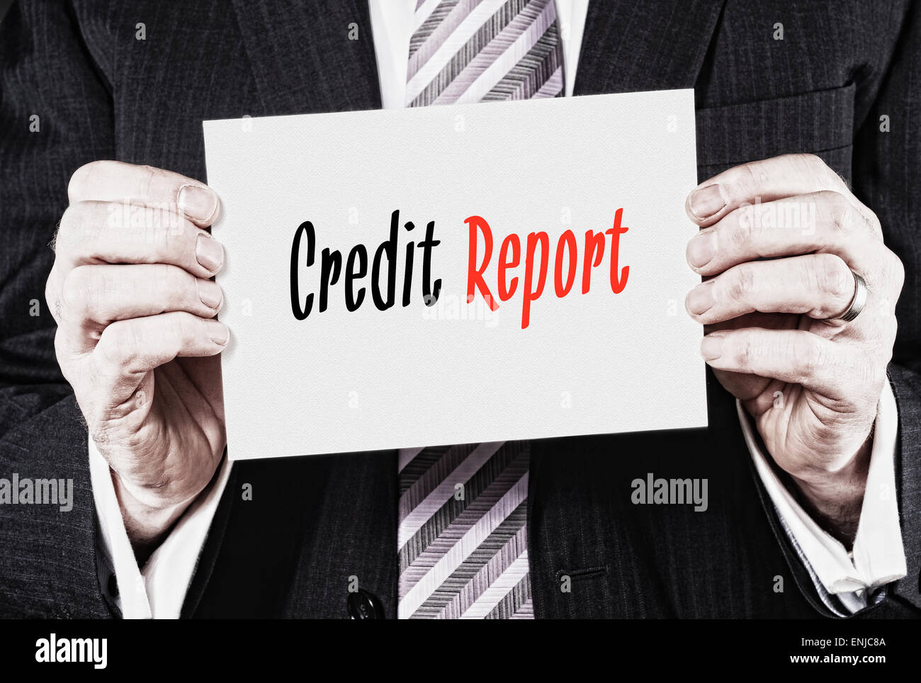 A businessman holding a business card with the words,  Credit Report, written on it. - Stock Image