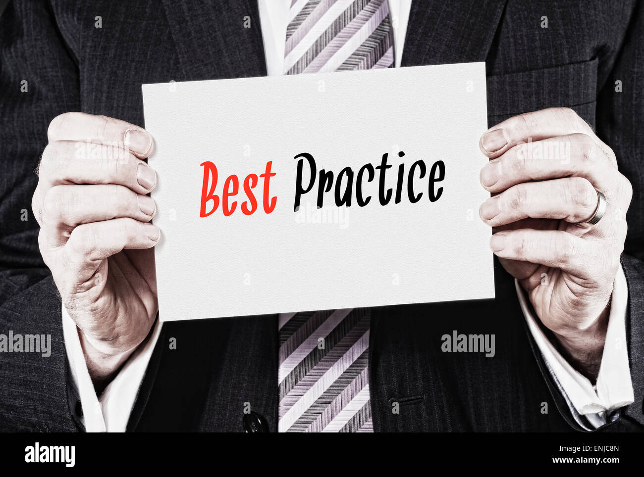 A businessman holding a business card with the words,  Best Practice, written on it. - Stock Image