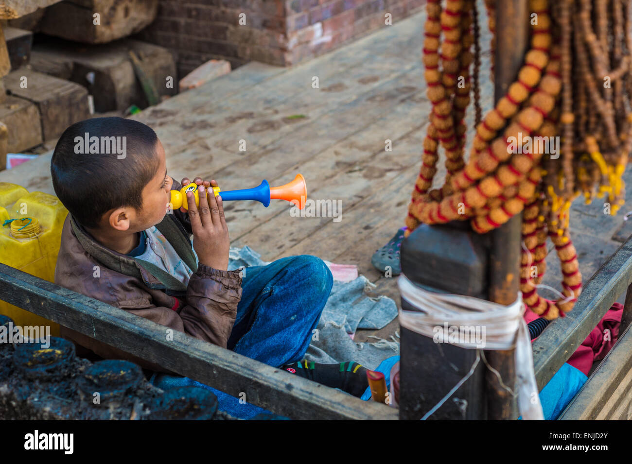 Nepali child playing with a trumpet toy - Stock Image